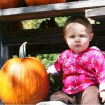Little girl sitting beside pumpkin 8.2010