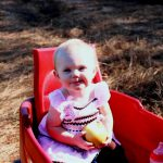baby in red wagon